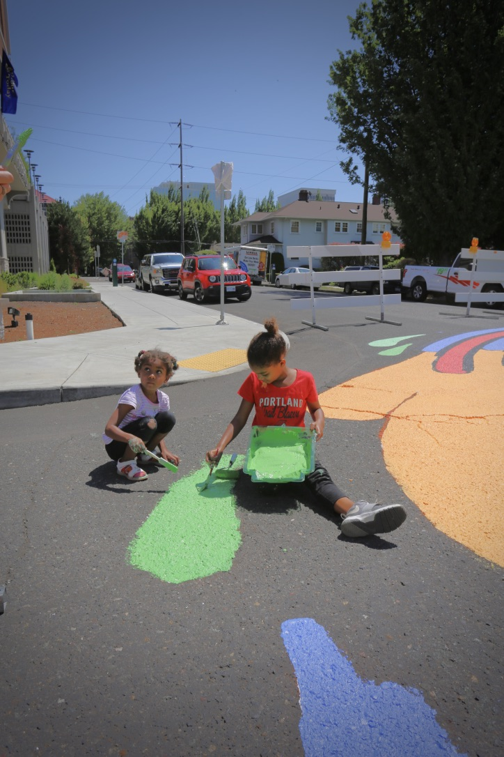 Kids with Color Outside the Lines help paint an intersection mural in Lloyd